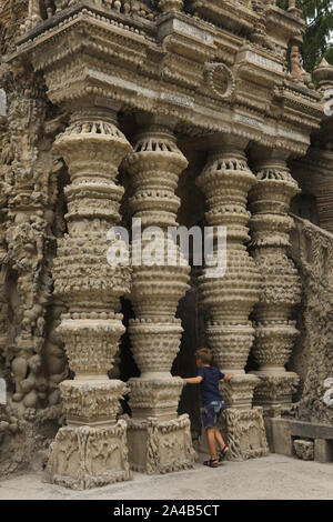 Young visitor in front of the entrance to the Ideal Palace (Le Palais idéal) designed by French postman Ferdinand Cheval and build from 1876 to 1912 in Hauterives, France. ATTENTION: This image is a part of a photo essay of 36 photos featuring the Ideal Palace (Le Palais idéal). - Stock Photo