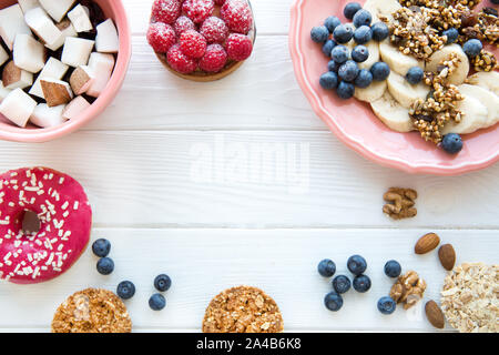 Healthy crunchy cookies and granola, banana and coconut pieces, pink doughnut and raspberry tart on white wooden table. Pastel colors, free space for - Stock Photo
