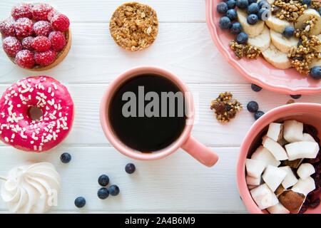 Different kinds of sweets and a cup of coffee on white wooden table background. Top view. - Stock Photo