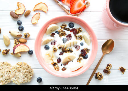 Bowl of healthy yogurt with fruits and berries, fresh banana, dried fruits, served with a cup of black coffee on white wooden background. - Stock Photo