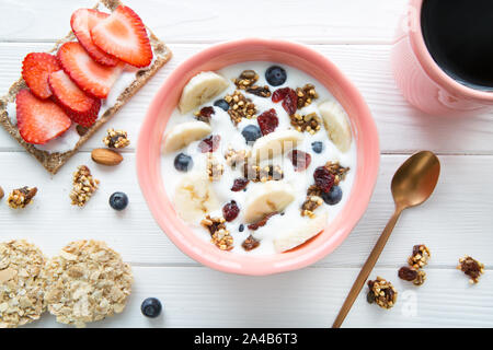 A bowl of fresh yougurt with granola, banana abd blueberry and a tasty fruit sandwich on white wooden table, top view. - Stock Photo