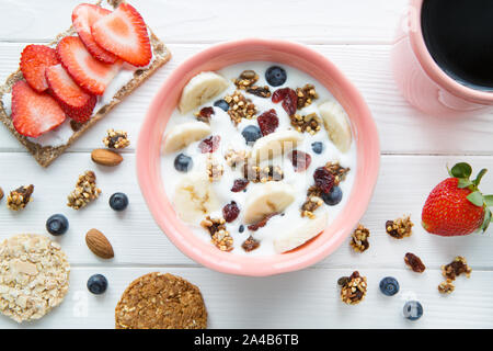 Healthy breakfast: yogurt with fruits and strawberry sandwich on white rustic table, top view. - Stock Photo