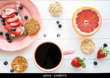 Tasty vegetarian breakfast, tasty sandwich with fresh strawberry and cheese, healthy oat cookies on white wooden table background. - Stock Photo
