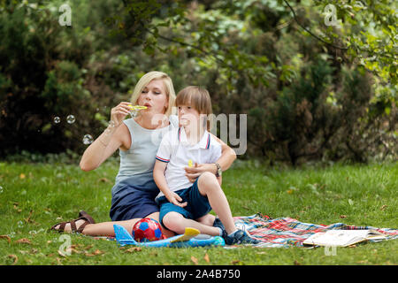 Young pretty woman and her challenged son having soap bubbles fun on a park lawn - Stock Photo