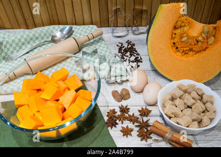 Fresh pumpkin (squash) on kitchen table with baking ingredients for cooking. A lot of spice, nuts and eggs, cane brown sugar. - Stock Photo