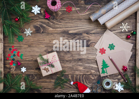 Christmas presents, gifts wrapping, postcards writing accessories, flat lay, wooden background with fir tree branches, paper, toys, cord. - Stock Photo