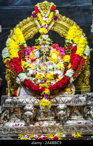 KUALA LAMPUR, MALAYSIA - DECEMBER 18, 2018: Beautiful statue of Hindu God Sri Ganesar with colorful floral decoration in Kortumalai Court Hill temple. - Stock Photo