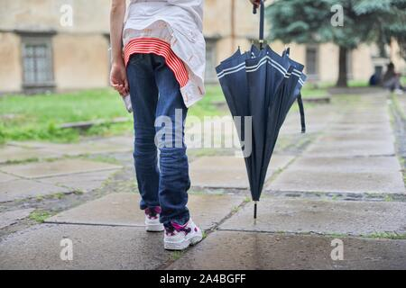 Rainy weather, legs of girl with an umbrella on wet paving stones after rain close-up - Stock Photo