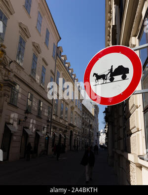 A street sign forbidding horse drawn carts down an urban street in shadow - Stock Photo