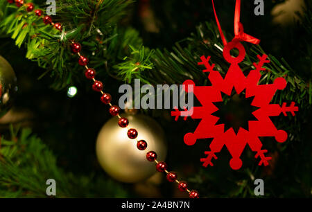 Star or snowflake symbol of deep red Christmas, hung on a Christmas tree with a red string of small balls and golden Christmas balls in the background - Stock Photo