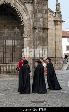 Braga, Portugal - September 17, 2019: Students in black robes talking with the tourists in front of Braga Cathedral (Sé de Braga) - Stock Photo