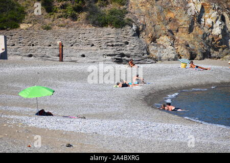 Adults and children spending a day on the beach in south of France.Pebbled beach great for paddling, swimming and sunbathing. Rocks at the background. - Stock Photo