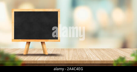 wood table with blank blackborard menu and blurred leaf foreground leaf in restaurant with bokeh background. product display template.Business present - Stock Photo