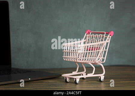 Grocery cart pink color on wooden desk and laptop with copy space for text. Shopping online promotion for Christmas new year, Valentine, black friday - Stock Photo