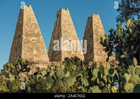 The cone shaped smelting towers of the shuttered mine of the Santa Brigida Hacienda in the ghost town of Mineral de Pozos, Guanajuato, Mexico. The town, once a major silver mining center was abandoned and left to ruin but has slowly comeback to life as a bohemian arts community. - Stock Photo