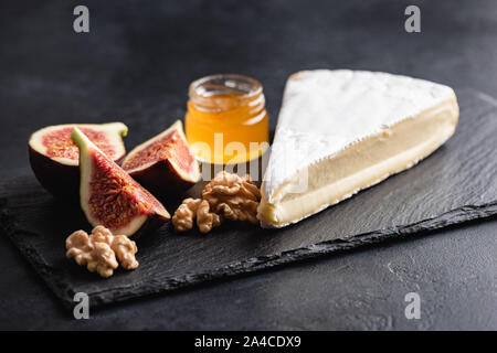 Brie or camembert cheese served with figs, honey and walnuts on black slate. Cheese plate - Stock Photo