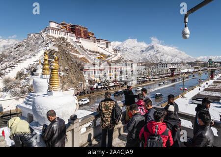 Lhasa, China - December 26 2018: Chinese tourist enjoy the view of the famous Potala Palace from the viewpoint in Lhasa in Tibet province on a sunny w