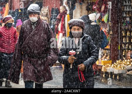 Lhasa, China - December 26 2018: Tibetan Buddhist woman performs a kora holding a prayer wheel around the  Jokhang temple in Lhasa old town in Tibet