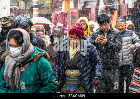 Lhasa, China - December 26 2018: Tibetan Buddhists devouts perform a kora around the  Jokhang temple  along Barkhor street in Lhasa old town in Tibet
