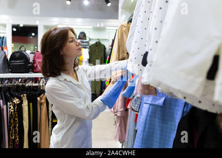 Young woman chooses clothes in clothing shop - Stock Photo