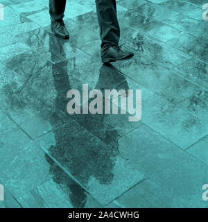 Blurry reflection legs and shadow, silhouette of a man in the wet sidewalk, in a puddle walking on a rain - Stock Photo