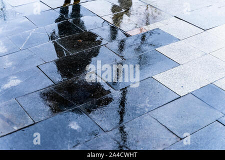Blurry reflection shadow silhouette of a woman walking under umbrella in a pedestrian city wet street in a puddle, autumn rainy evening