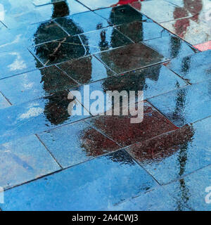 Blurry reflection shadows silhouettes of a woman under umbrella and a man walking in the rain in the city sidewalk, autumn rainy evening - Stock Photo