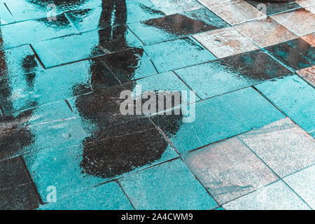 Blurry reflection shadow silhouette of a girl walking under umbrella in a pedestrian city wet street in a puddle, autumn rainy evening - Stock Photo