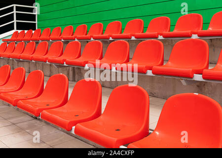 Rows of red diagonal spectator seats with no people in it - Stock Photo