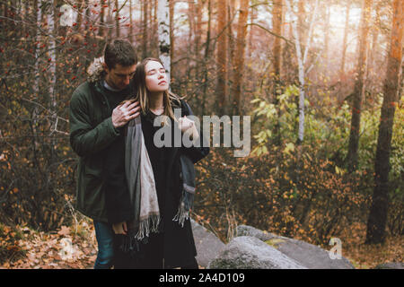 Young couple in love friends dressed in casual style walking together on nature park forest in the cold season