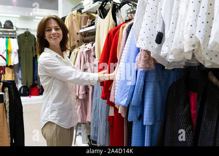 Young happy woman chooses clothes in clothing shop - Stock Photo