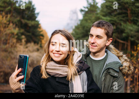 Happy young couple in love friends travellers dressed in casual style making selfie on the nature park forest - Stock Photo