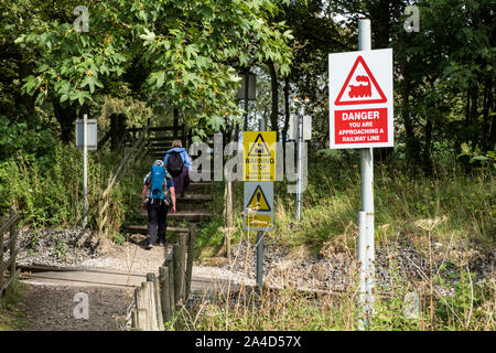 People crossing railway line. Warning signs next to the railway track, Hope, Derbyshire, England, UK - Stock Photo