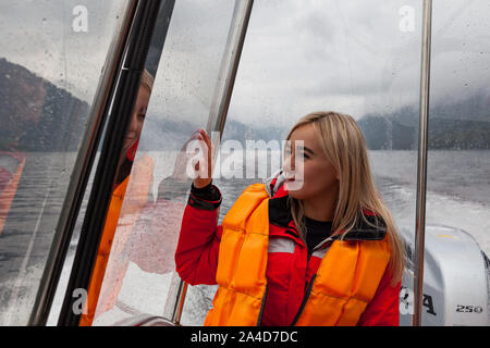 Beautiful young blonde woman in an orange life jacket sits in a motor boat during an excursion and sailing on Lake Teletskoye in the Altai mountains. - Stock Photo