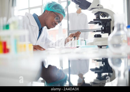 Side view portrait of African-American man working in laboratory preparing test samples in petri dish for medical research, copy space - Stock Photo