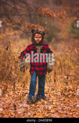 Portrait of a boy standing in forest dressed as a werewolf for Halloween, United States - Stock Photo