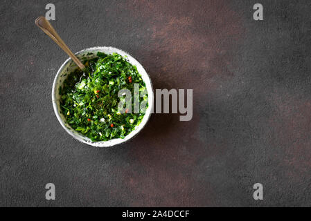 Raw homemade chopped green Chimichurri or Chimmichurri sauce made of parsley, garlic, oregano, hot pepper, olive oil, vinegar, on rustic table, top vi - Stock Photo