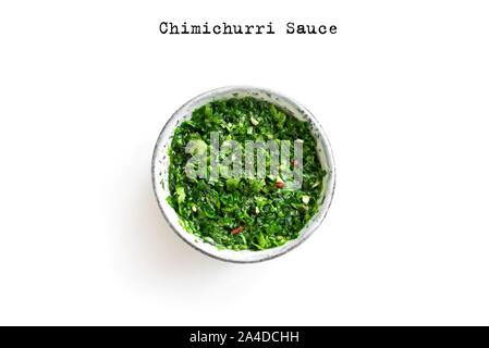 Raw homemade chopped green Chimichurri or Chimmichurri sauce made of parsley, garlic, oregano, hot pepper, olive oil, vinegar, isolated on white, top - Stock Photo