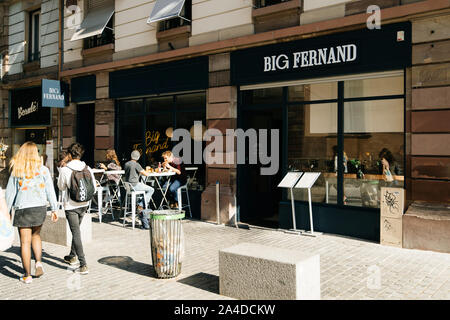 Strasbourg, France - Sep 21, 2019: Big Fernand hamburger chain restaurant with pedestrians walking and customers eating inside and at the outdoor terrace - Stock Photo