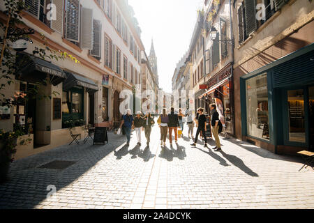 Strasbourg, France - Sep 21, 2019: Street view cityscape of Rue des Juifs street with shops people restaurants and Notre-Dame de Strasbourg cathedral in background - Stock Photo
