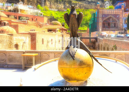Tbilisi, Georgia - April 24, 2017: Bird statue and Sulfur Baths houses of Old Town of Tbilisi, Republic of Georgia - Stock Photo