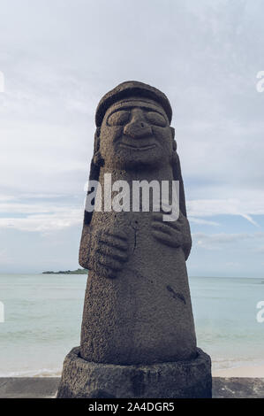 Jeju Island, South Korea, september 05, 2019: View of one of the Dol Hareubang on Geumneung  beach with sea behind it - Stock Photo