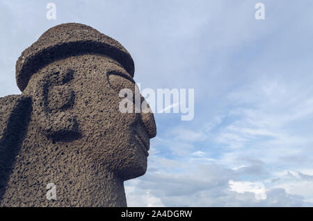 Jeju Island, South Korea, september 05, 2019: profile view of Dol Hareubang on Geumneung beach with beautiful cloudscape on background - Stock Photo