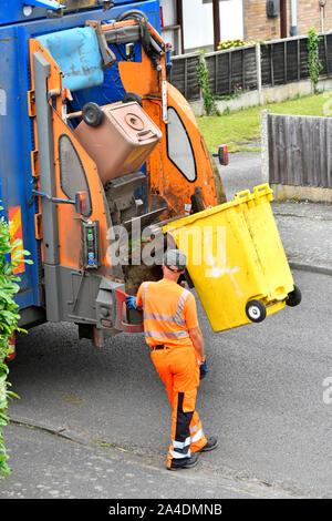 Refuse collection wearing high vis clothes operates lifting up controls back of dustcart to empty wheelie bin full of  green garden recycling waste UK - Stock Photo