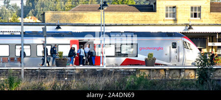 Group of early morning commuter people on Ely railway station platform at 7.29am boarding Greater Anglia train carriage  Cambridgeshire England UK - Stock Photo