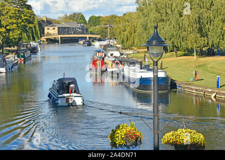 View of part of Great River Ouse at Ely with small motor boat passing moored narrow boats sunny summer afternoon Cambridgeshire East Anglia England UK - Stock Photo