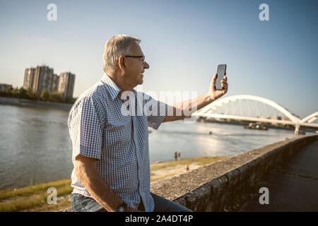Outdoor portrait of senior man who is taking selfie. - Stock Photo
