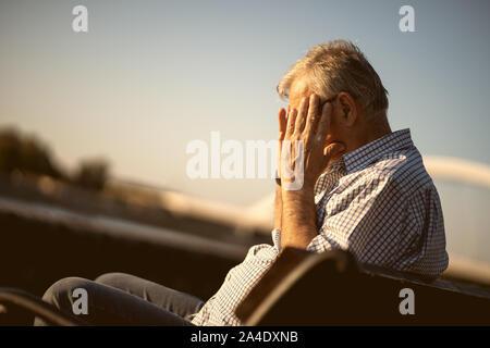 Outdoor portrait of senior man who is having headache. - Stock Photo