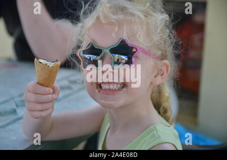 Young girl eating ice cream in sunglasses - Stock Photo