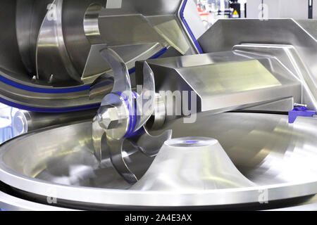 Cutter for chopping meat at a meat processing plant. Industrial cutter at the factory where sausages are made. Huge stainless-steel pars for meat proc - Stock Photo
